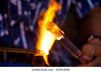 Workers are using the heat of gas blowing glass to look as art, shape, light, flame beautiful.