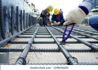 Workers are using steel wire to bind steel bars for foundation structures in the chemical plant construction area. - Shutterstock ID 1598236435