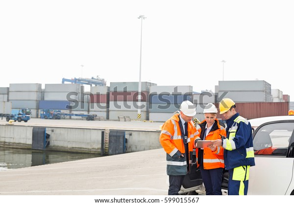 Workers using tablet PC beside car in shipping yard