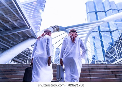 The workers walk on the steps. Businessmen go to their office. Arab businessman is talking with his colleague or friend,  They're successful of career with cityscape, lens flare, sunlight background.