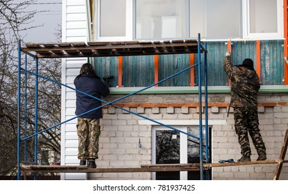 Workers walling the house with wall siding