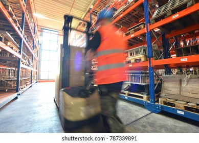 workers in the warehouse of a company with forklift trucks - speed in logistics - blurred movement