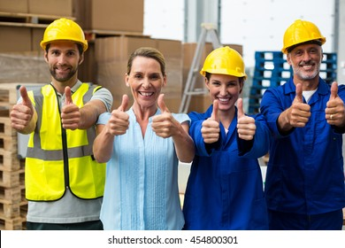 Workers at warehouse with thumbs up