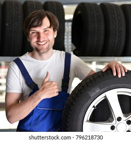 workers in a warehouse with tyres for changing the car