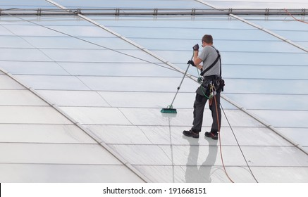 Workers washing the roof made of glass of a modern office building