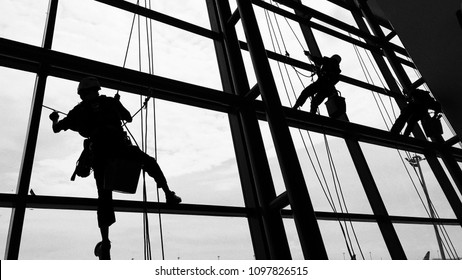 Workers are washing windows of the airport terminal from heights