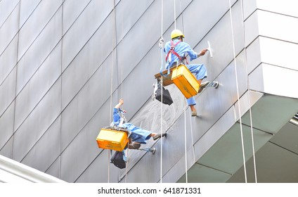 workers washing windows of the modern skyscraper