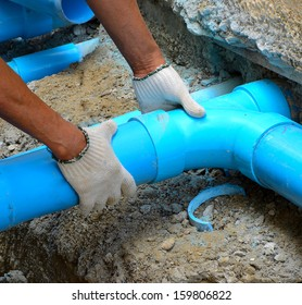 Workers are water pipes with PVC joints Elbow allows the split to the left or right, which must penetrate concrete walls to make PVC pipe coming out the other side of the building.