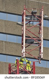 Workers wearing safety harness reaching for lifted element of a tower crane
