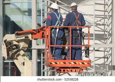 Workers wearing safety harnesses on an aerial access platform