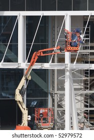 Workers wearing safety harnesses on an aerial access platform at a construction site