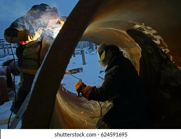 Workers are welding inside and outside of the pipe