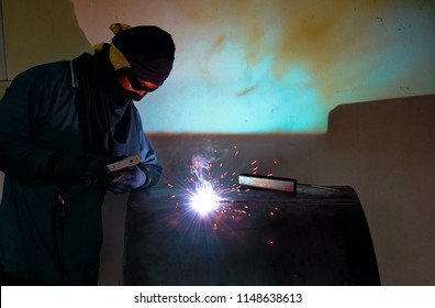 Workers are welding steel pipes that cause sparks and smoke from welding. Concepts for the industry.