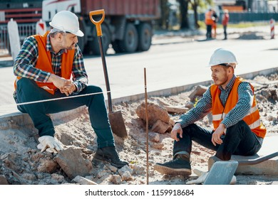 Workers in white helmets and reflective vests during a break on roadwork