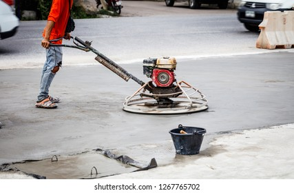Workers who are polishing cement floors in construction