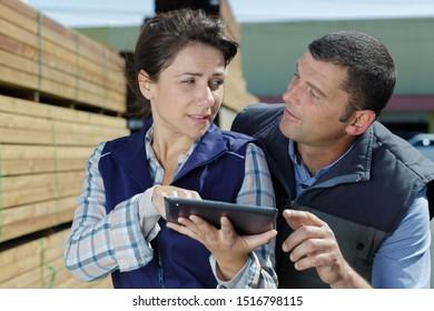 workers in woodyard looking at tablet