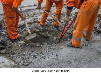 workers work on the replacement of cover slab with cast iron cover on the road with the help of a shovel and Bolt Cutter