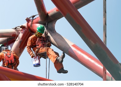 Workers working at height to paint the jack up oil and gas rig with full personnel protective equipment