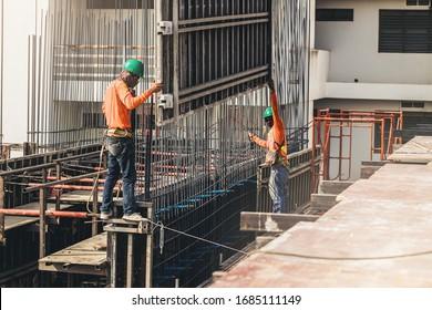 Workers are working on construction site, labourers wearing vest and safety helmet, construction crews on steel work at the building