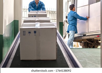 Workers are Working in Warehouse.Cardboard Boxes on Conveyor Belt in warehouse.