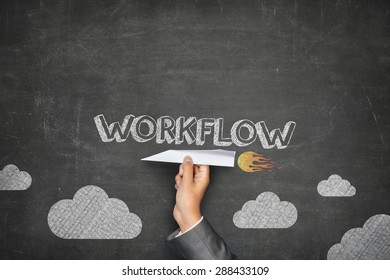 Workflow concept on black blackboard with businessman hand holding paper plane