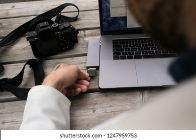Workflow or creative process of freelance photographer or director. Export or transfer data files, images and videos from camera to laptop through multifunctional adaptor or cardreader