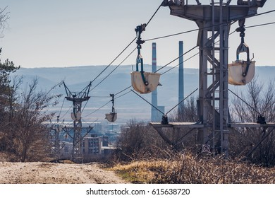 Working Aerial Rope-way Carrying White Stone to the Plant on the Background of Hills
