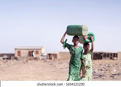 Afrikanische Ethnizitäts-Schülerin, die Frischwasser aus Mangel an Wasserzeichen sammelt