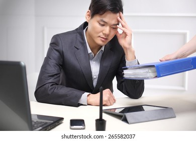 Working after hours, stress and fatigue.Handsome man in business suit sitting at his desk in his study supports the head in his hands.