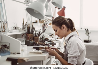 Working all day. Side view of young female jeweler sitting at her jewelry workshop and holding in hands jewelry tools for making accessories