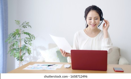 Working asian woman in the living room. Telemeeting. Video conference. Remote work.
