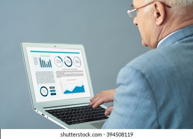 Working atmosphere. Close up shot of experienced old man holding laptop and making up business report.
