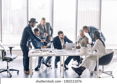 Working atmosphere in the office, focus on caucasian chief executive being surrounded by his deputies and assistants, sitting at desk and working together.