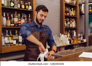 Working barman. Calm professional barman carefully cleaning the glasses while standing at the bar counter
