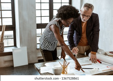 Working with boss. Young African-American trainee of interior design company working with boss