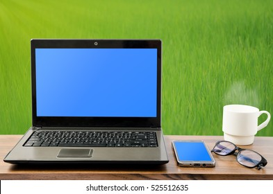 Working by black laptop computer with blue screen, smart phone, spectacles eyeglasses, and hot coffee with steam in white coffee cup on wooden table in beautiful green rice field in morning