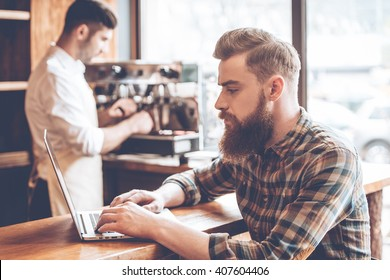 Working in cafe. Side view of young handsome bearded man using his laptop while sitting at bar counter at cafe with barista at the background