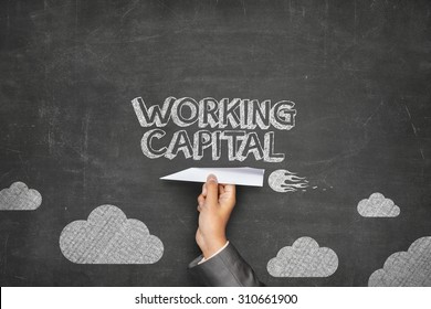 Working capital concept on black blackboard with businessman hand holding paper plane
