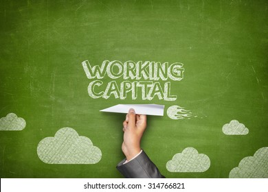 Working capital concept on green blackboard with businessman hand holding paper plane