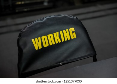 Working chair at a sporting event with a black cover and yellow text writing.