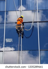 a working climber is working on a glass wall of a high-rise building