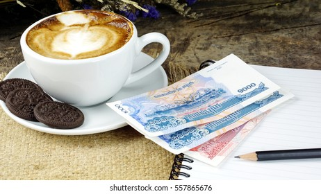 Working with Coffee. A cup of latte, cappuccino or espresso coffee with milk put on a wood table with cookies, notebook, pencil and Cambodia Banknote.