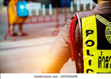 Working concepts of Thai police : The police are responsible for the safety of Thai monks : Blurred background : In Thai, read as Tảrwc. The English translation is police.