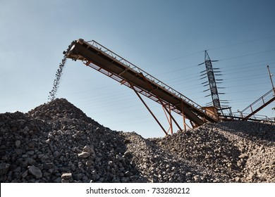 Working conveyor belt on slag transportation and loading. Heavy industrial metallurgical landscape with power lines on background