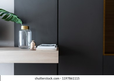 working corner decorated with books and artificial plant in gold collar glass vase on gray spray painted warbrobe / cozy interior concept / isolated for advertising