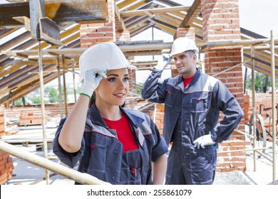 working couple - woman and man - two Young adult builders on a background of iron metal beam roof trusses and summer city town with green trees at street , blue sky with clouds on backdrop