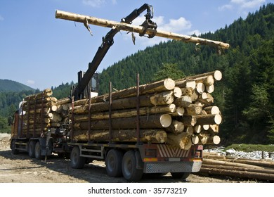 working crane in a forest building a stack of logs