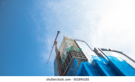 Working crane and safety net on a modern office and residential building under construction against blue sky in Hanoi, Vietnam. Green grid prevent objects from falling. Industrial Background. Panorama