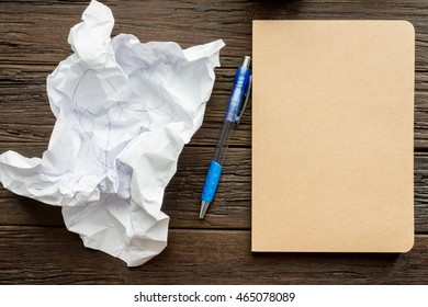 Working with crumpled paper, pen and book on wooden table background