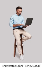 Working day. Full length of good looking young man smiling and using computer while sitting on stool against grey background